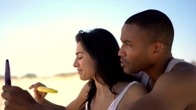 Couple eating ice creams while talking at beach