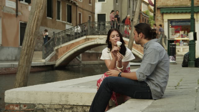 ms couple eating ice cream,sitting on water's edge in old town / venice,veneto - moving activity stock videos & royalty-free footage