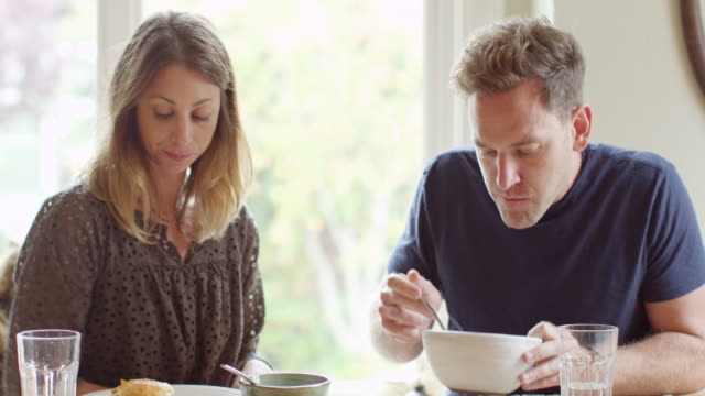 MS Couple eating lunch together near window in home