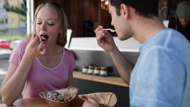couple eating outside at food truck - foodie stock videos & royalty-free footage