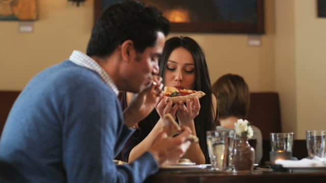couple eating pizza at a fancy restaurant - pizza stock videos & royalty-free footage
