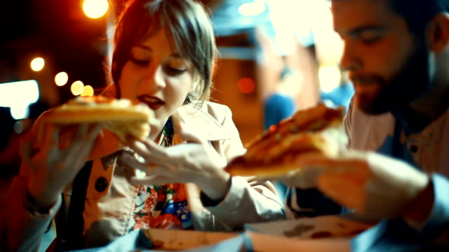 vidéos et rushes de couple, manger pizza en plein air le soir. - unhealthy eating