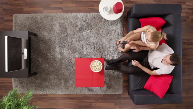 MS, couple eating popcorn and watching TV in their living room, overhead view