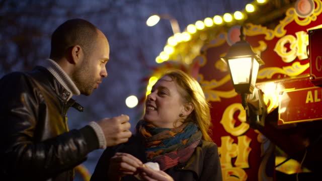 a couple eating roast chestnuts at a fun fair - marrone video stock e b–roll