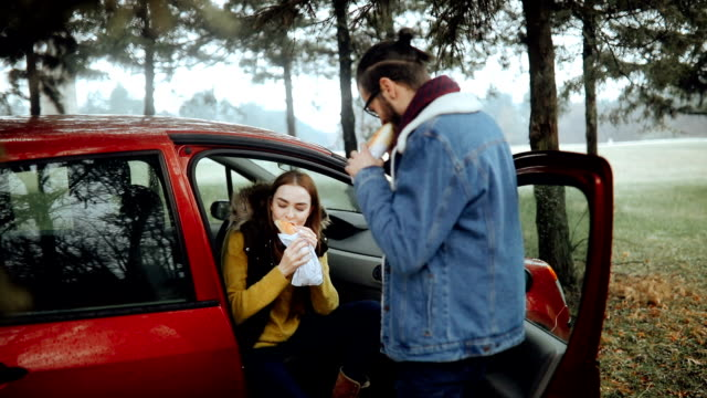 Couple eating sandwich in their car on a break from driving