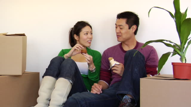 MS Couple eating snacks and resting against wall in between moving boxes / Los Angeles, California, USA