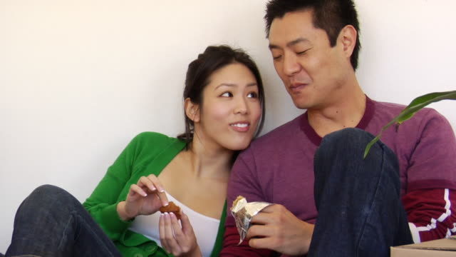 cu couple eating snacks and resting against wall / los angeles, california, usa - protein bar stock videos & royalty-free footage