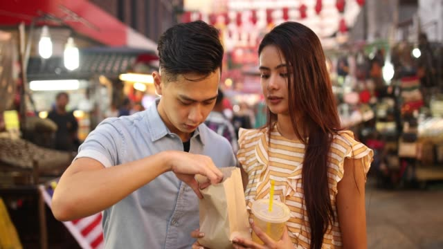 couple eating street food at the jalan petaling market - east asian culture stock videos & royalty-free footage