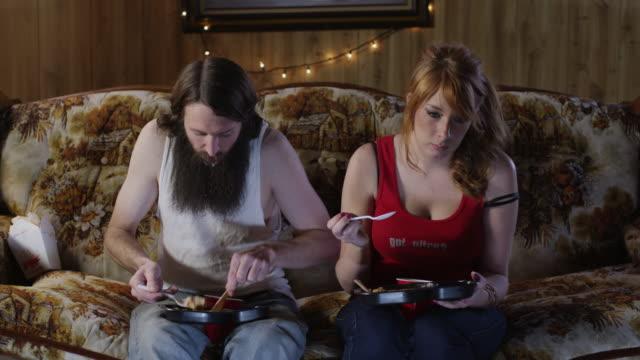 ms couple eating take away food on sofa at christmas / orem, utah, usa - orem utah stock-videos und b-roll-filmmaterial