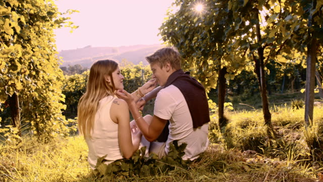 Couple eating white grapes in the vineyard