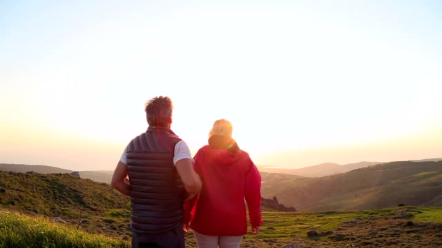 Couple embrace looking out at the sea above green hillsides