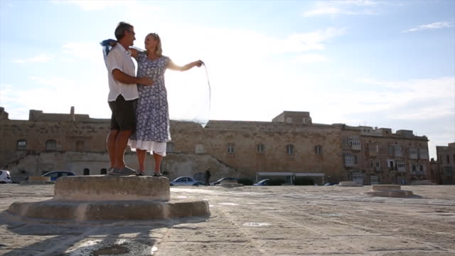couple embrace on raised pedestal, piazza, valletta - malta stock videos & royalty-free footage