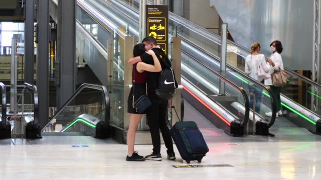 couple embraces and kisses at the exit door of the arrivals terminal at the adolfo suarez madrid barajas airport on june 21, 2020 in madrid, spain.... - embracing stock videos & royalty-free footage