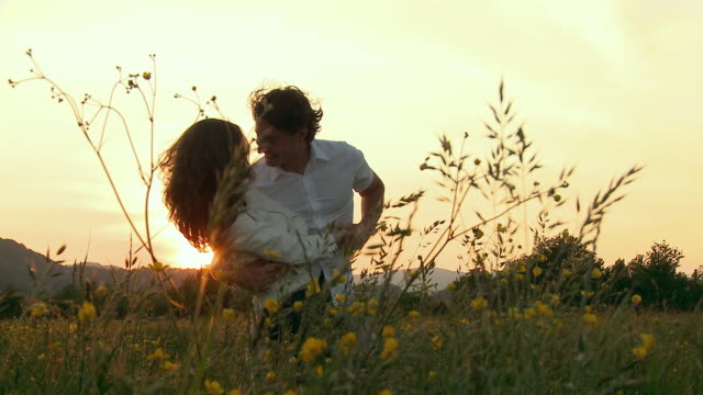 ms pan couple embracing and dancing in meadow at sunset / vrhnika, slovenia - alm stock-videos und b-roll-filmmaterial