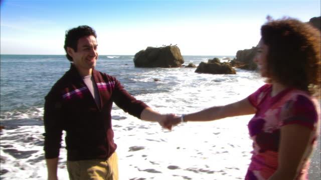 cu, tu, couple embracing and dancing in rocky beach, moonstone beach, cambria, california, usa - norra stilla havet bildbanksvideor och videomaterial från bakom kulisserna