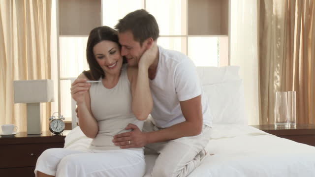 MS Couple embracing and kissing after looking at pregnancy test, sitting on bed / Cape Town, Western Cape, South Africa