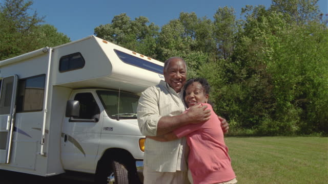 MS LA Couple embracing and kissing in front of parked motor home / Asheville, North Carolina, USA