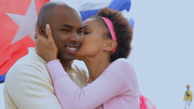 vídeos de stock, filmes e b-roll de ms couple embracing and waving, cuban flag in background / havana, cuba - vínculo