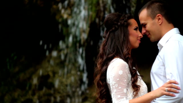Couple embracing by waterfall