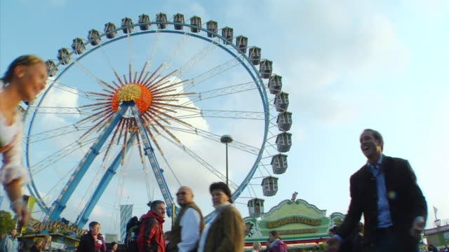 slo mo couple embracing in front of big wheel at oktoberfest fair / munich, bavaria, germany  - german culture stock videos and b-roll footage
