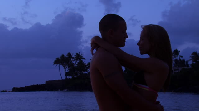 couple embracing in front of water outdoors at night - turtle bay hawaii stock videos and b-roll footage