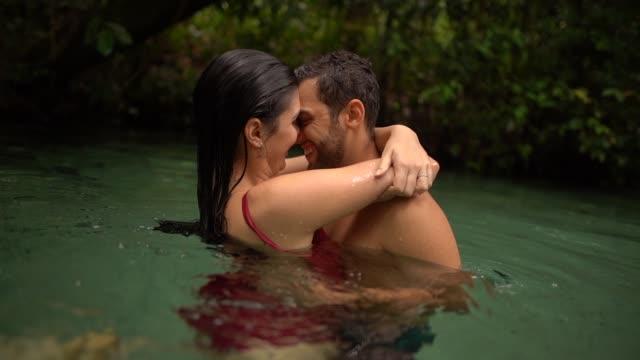 vídeos de stock, filmes e b-roll de acople o abraço no rio - beijando