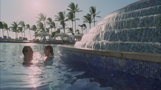 MS, Couple embracing in swimming pool in luxurious resort, Maui, Hawaii, USA