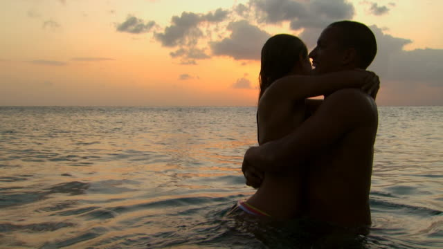 couple embracing in water at sunrise or sunset - see other clips from this shoot 1142 stock videos & royalty-free footage