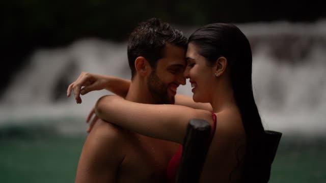 vídeos de stock, filmes e b-roll de acople o abraço na cachoeira - vale