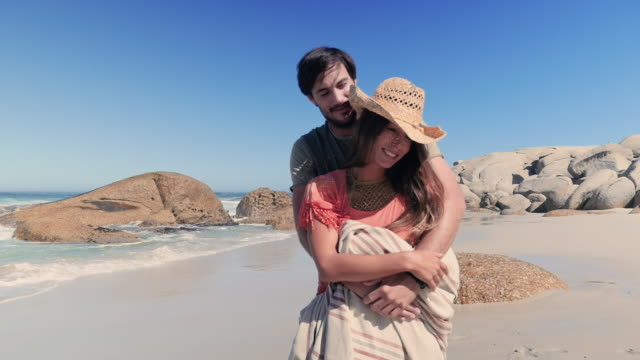 couple embracing on beach - タオルにくるまる点の映像素材/bロール