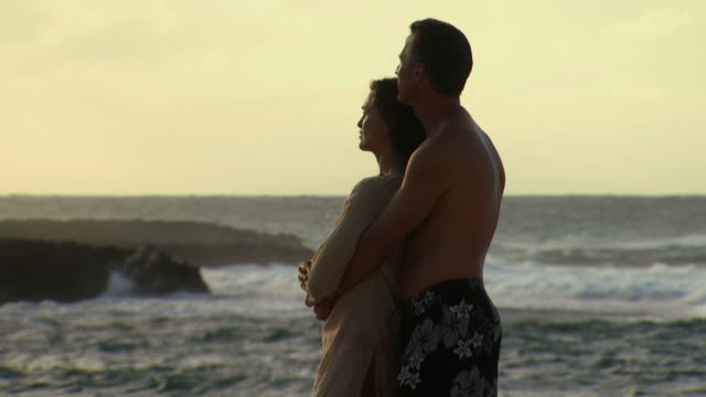 couple embracing on beach with waves - see other clips from this shoot 1142 stock videos & royalty-free footage