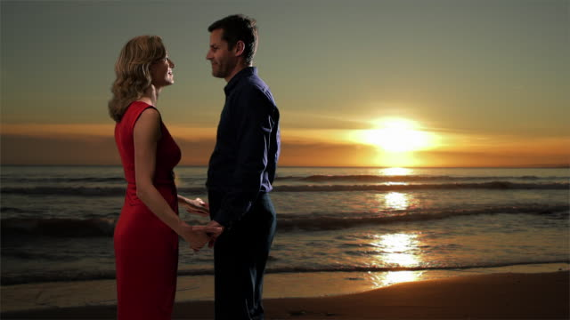couple embracing on the beach at sunset/marbella region, spain - tre quarti video stock e b–roll