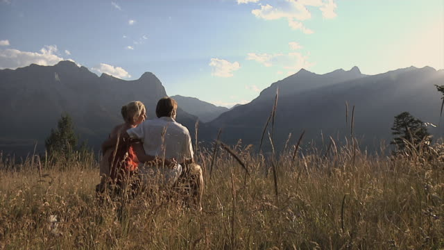 WS, couple embracing sitting in long grass field, Canmore, Alberta, Canada