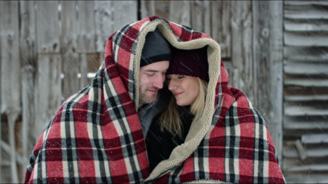 vídeos y material grabado en eventos de stock de couple embracing under a blanket outdoors during a winter storm - a cuadros