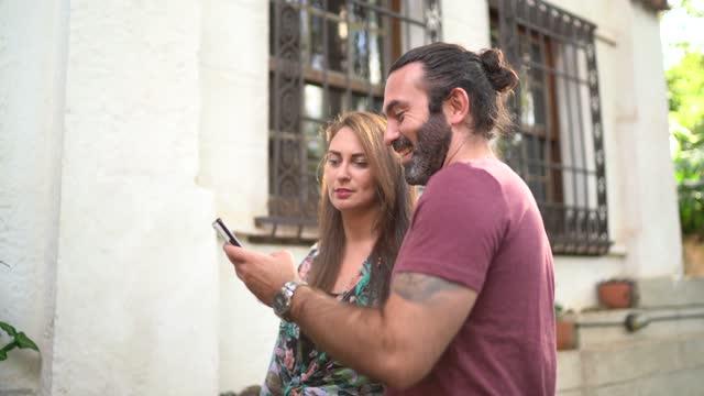 vídeos y material grabado en eventos de stock de pareja abrazando usando el teléfono inteligente al llegar al albergue - alojamiento y desayuno
