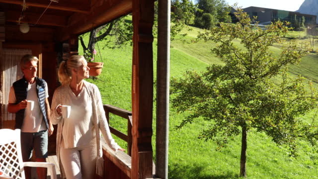 vidéos et rushes de couple emerge onto chalet deck with mugs of hot beverage - chalet