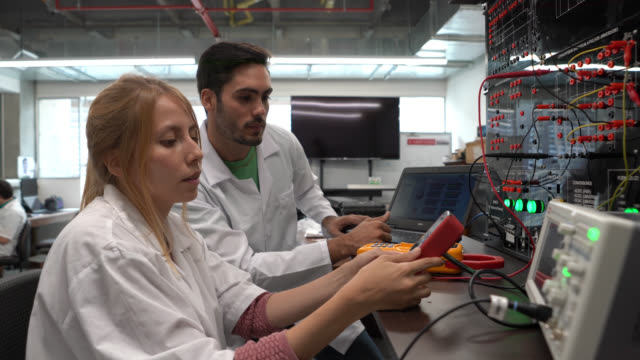 couple engineer students working on a project with electrical equipment at the lab - post secondary education stock videos & royalty-free footage