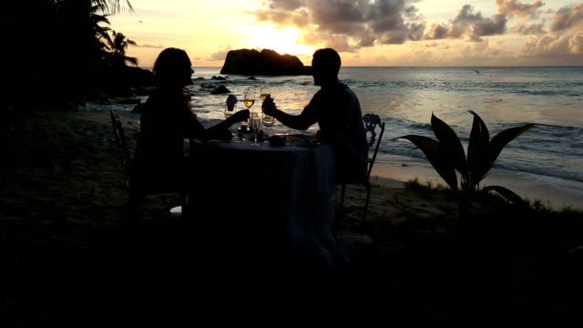 vídeos de stock, filmes e b-roll de a couple enjoy a romantic dinner on cousine island as the sun sets. - oceano índico