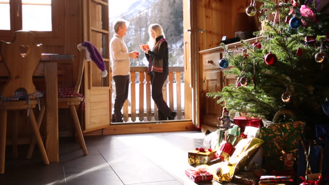couple enjoy hot drinks on veranda, christmas tree in front - ornament stock videos and b-roll footage