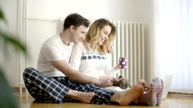 HD: Couple profiter Pajams avec leur chien à la maison.
