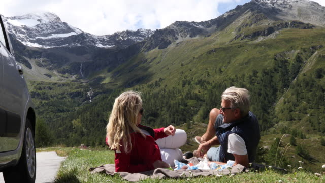 couple enjoy picnic in meadow alongside car, mountains - finding stock videos & royalty-free footage