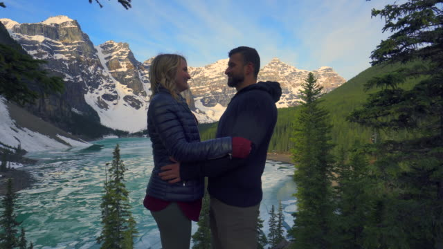 couple enjoy romantic moments beside beautiful mountain lake - down jacket stock videos and b-roll footage