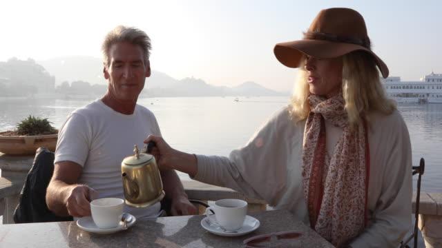 couple enjoy tea above lakeshore at sunrise - teapot stock videos & royalty-free footage