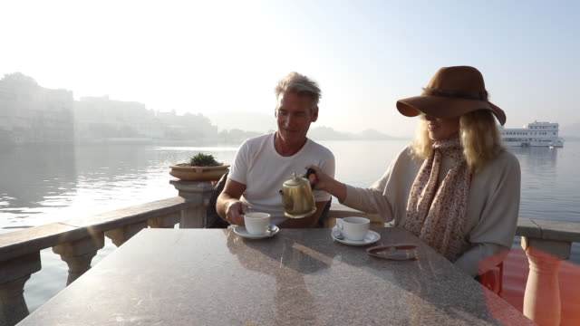 couple enjoy tea above lakeshore at sunrise - mature couple stock videos & royalty-free footage