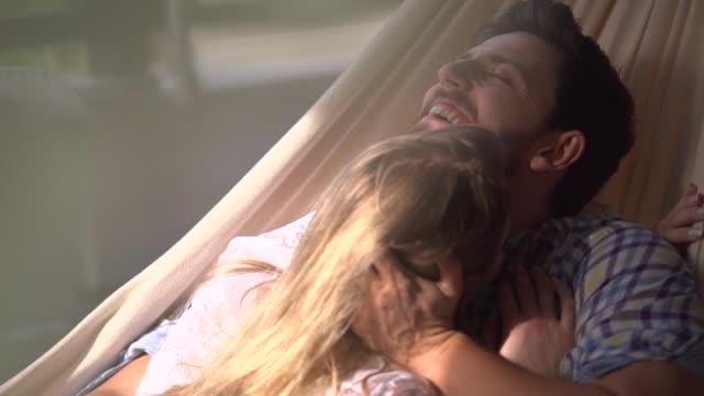 paar genießen ihre liebe, während sie in einer hängematte liegen - hängematte stock-videos und b-roll-filmmaterial