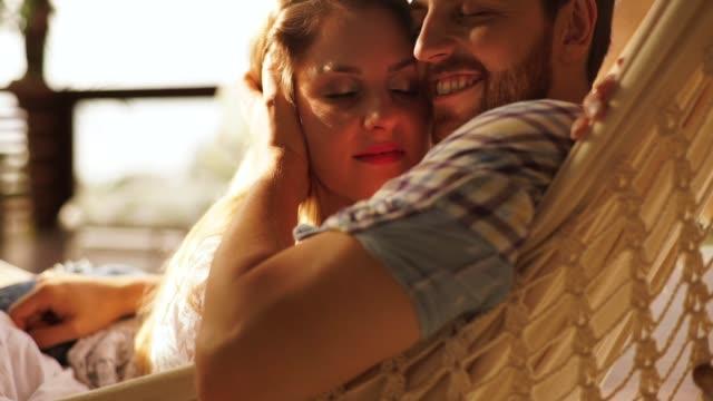 vidéos et rushes de le couple apprécie leur amour tout en se couchant dans un hamac - tomber amoureux