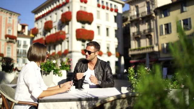couple enjoying a coffee rest in a town square - coffee drink stock videos & royalty-free footage