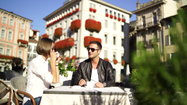 couple enjoying a coffee rest in a town square - square stock videos & royalty-free footage