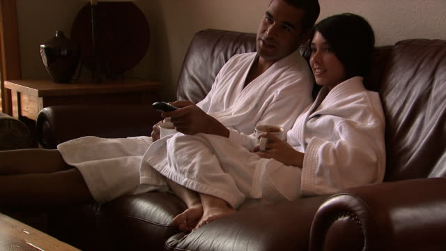 a couple enjoying a cup of coffee together watching television - pacific islander couple stock videos & royalty-free footage
