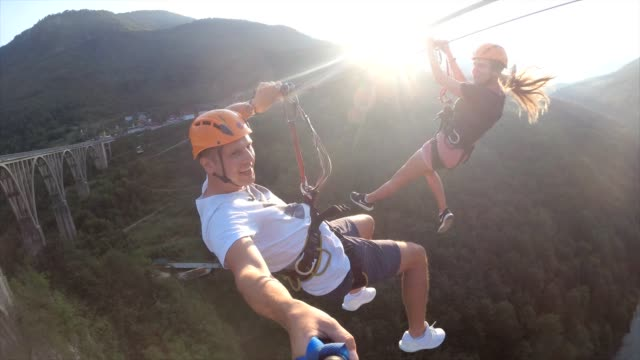 couple enjoying a ride on the zipline - zip line stock videos & royalty-free footage